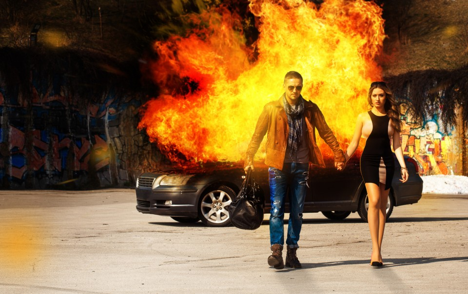 Horizontal picture of the blockbuster as a man and a woman go away from burning car outdoors